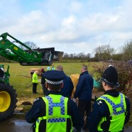 Dorset Police watch as a tractor trailer dismantles the activist site