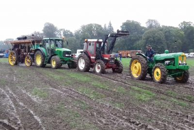 Three tractors towing a nine ton steam engine out of the mud
