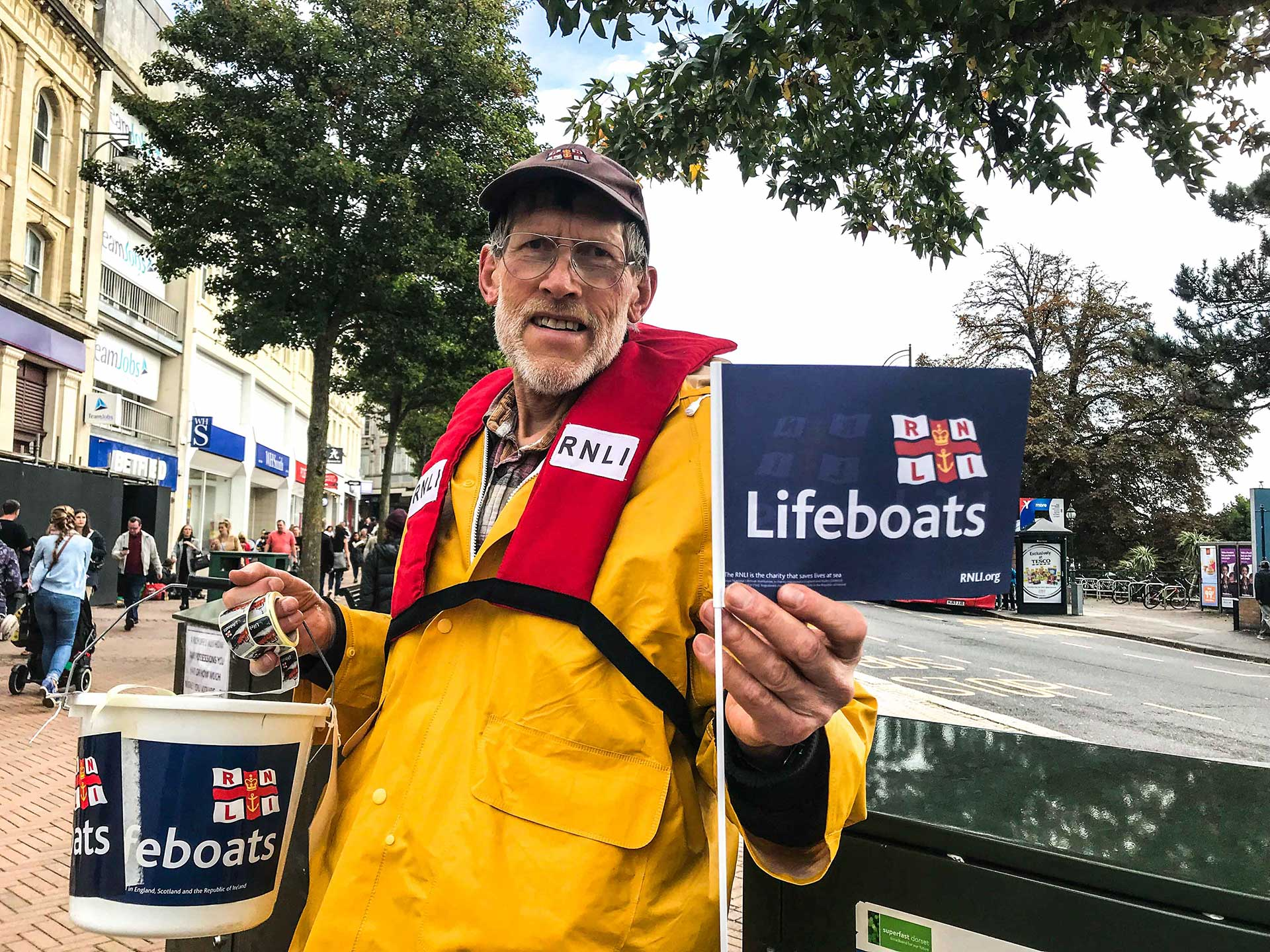 David Cox, with his Lifeboats basket and flag, always keep his smile and warmly welcome the passers-by on the street