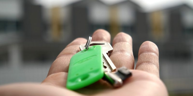 keys in hand and houses in the background