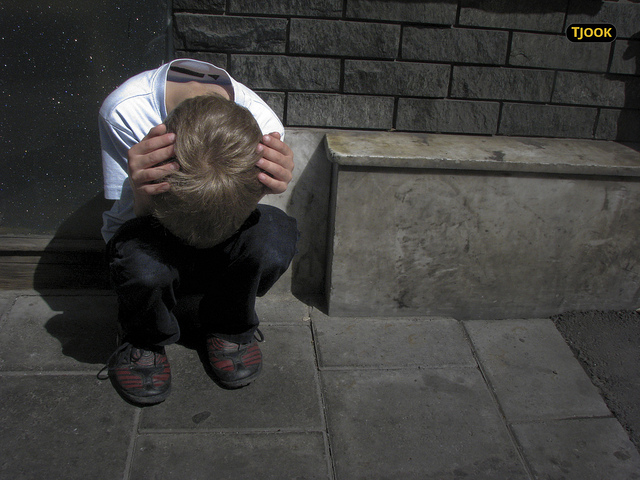A young boy huddled down in despair