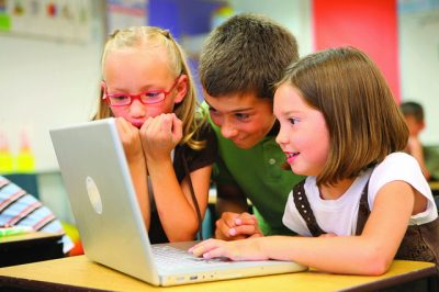 An image of children enjoying themselves on a laptop