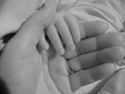 A greyscale image of a mother's hand touching her child's