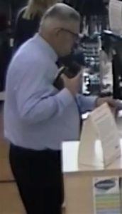 A CCTV image of a middle-aged man using a credit card in a shop