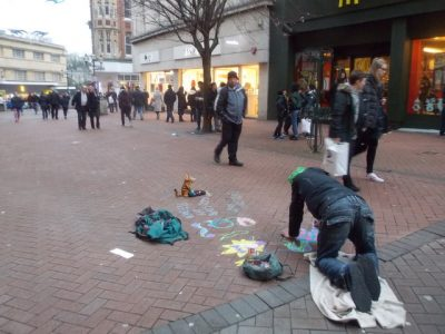 "Photo: Homeless man chalks art on the pavement. ""Homeless art beats begging""."