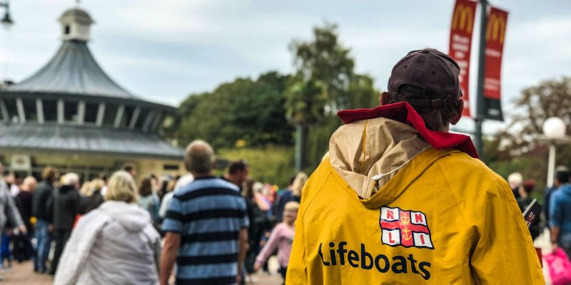 A local volunteer standing in Bournemouth Square and wearing a yellow crew kit