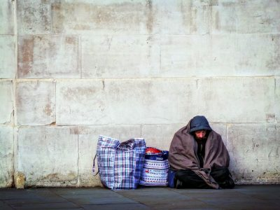 Homeless man sat by wall