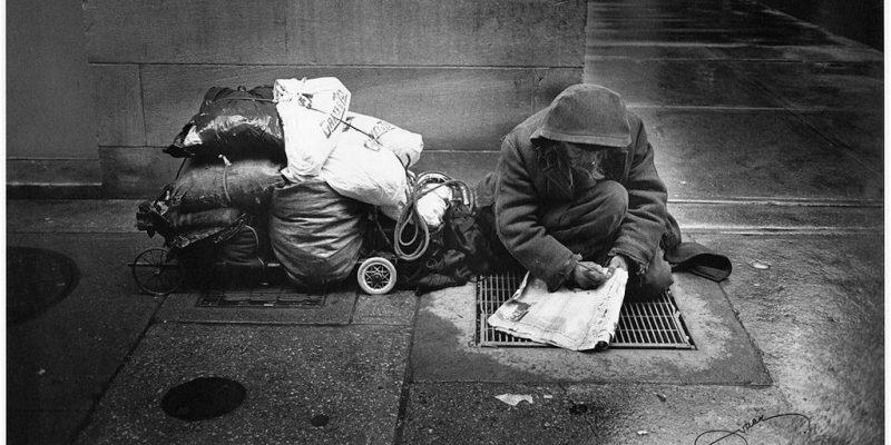 Homeless man doing crossword
