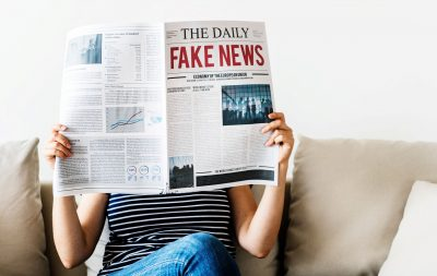 Photograph of Woman reading newspaper with Fake News Headline