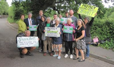 Campaign group standing with placards in front of a field