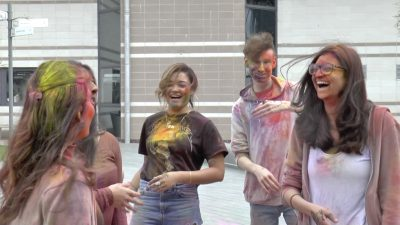 people laughing covered in colours