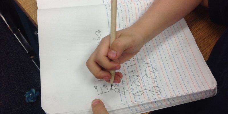 Child writing in school book
