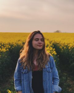 A girl stood in a field of flowers