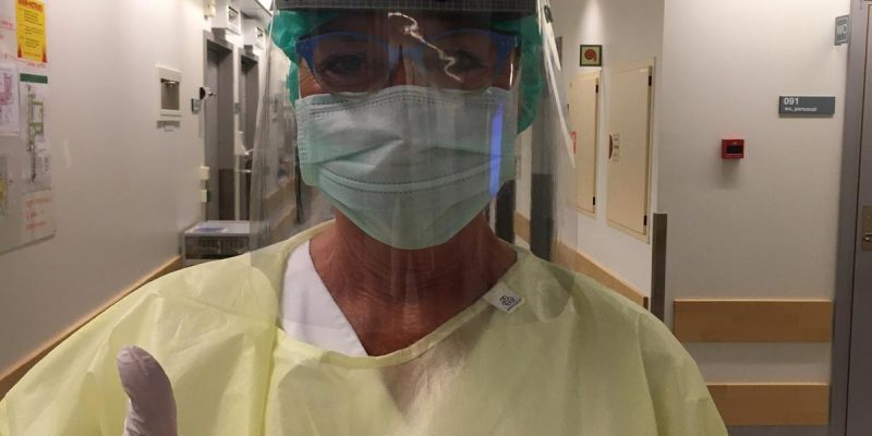Protective gear could be sweaty for some nurses, but Anne Karine Swanstroem is in a good mood.