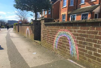 An image of rainbows drawn in chalk on a wall outside a home