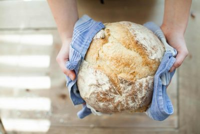 A woman holds a fresh loaf of bread