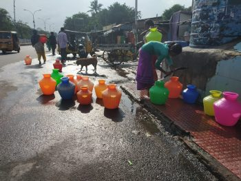 People collecting water from public water tanks
