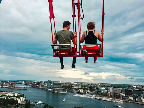 Two people swing over the city